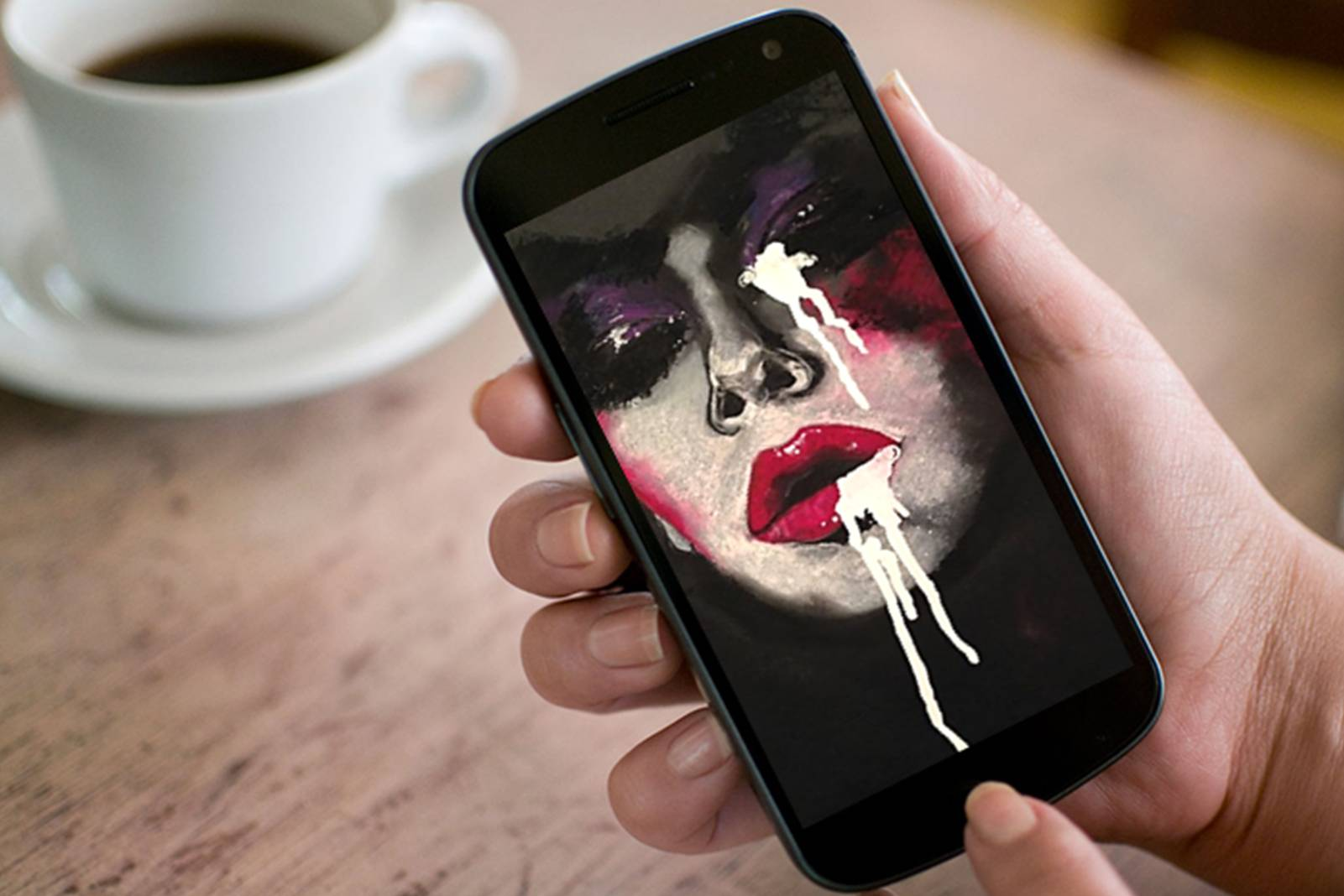 painting on mobile phone being held by woman