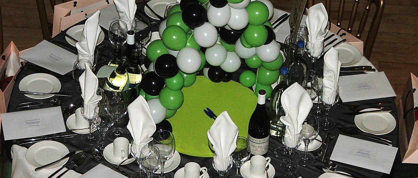 dinner table, balloons, wine, glasses plates, cutlery