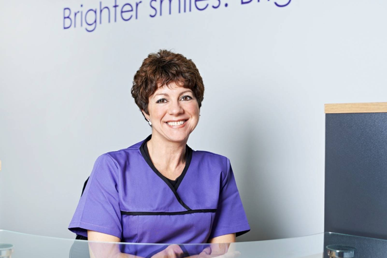 smiling woman sitting at reception