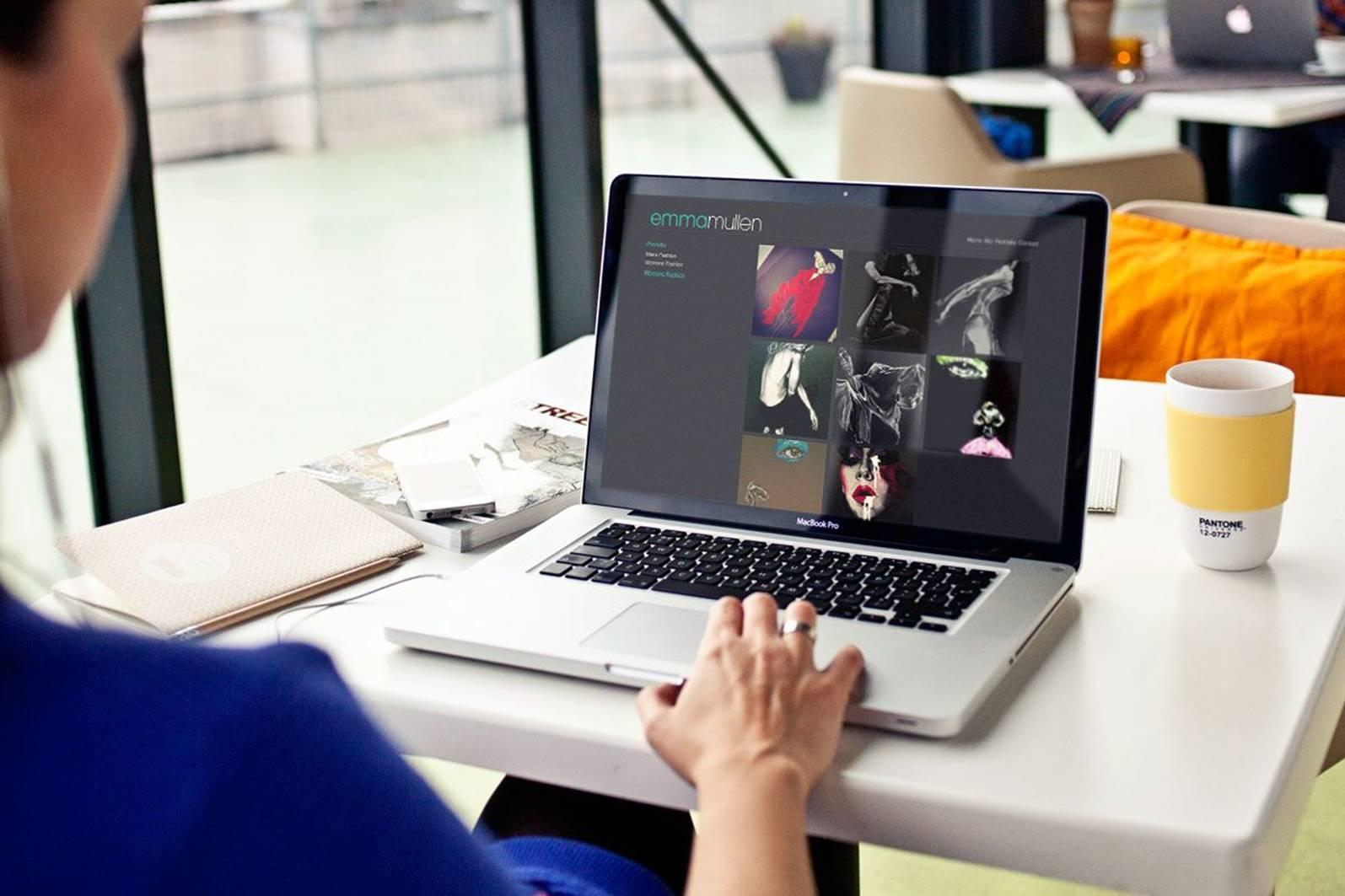 woman typing, white desk, laptop, cup, pencil, orange cushion