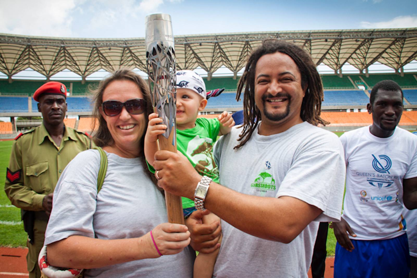 people smiling, holding commonwealth torch inside stadium