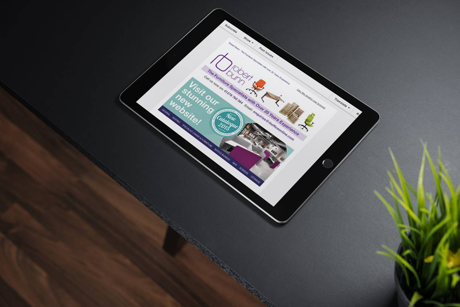 black computer tablet on desk with foliage
